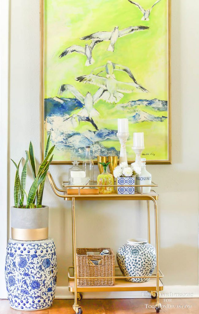 large green bird painting with gold bar cart