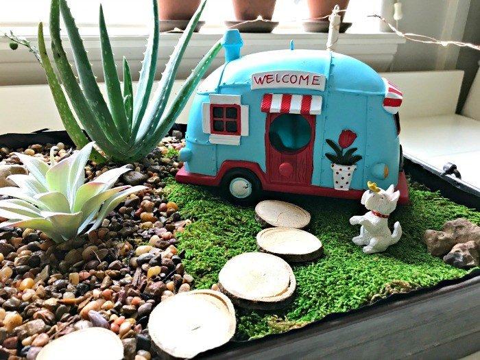 indoor outdoor succulent garden with miniature camper