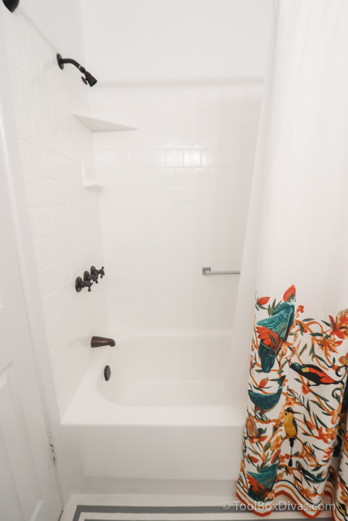 white painted tub and tile with colorful shower curtain