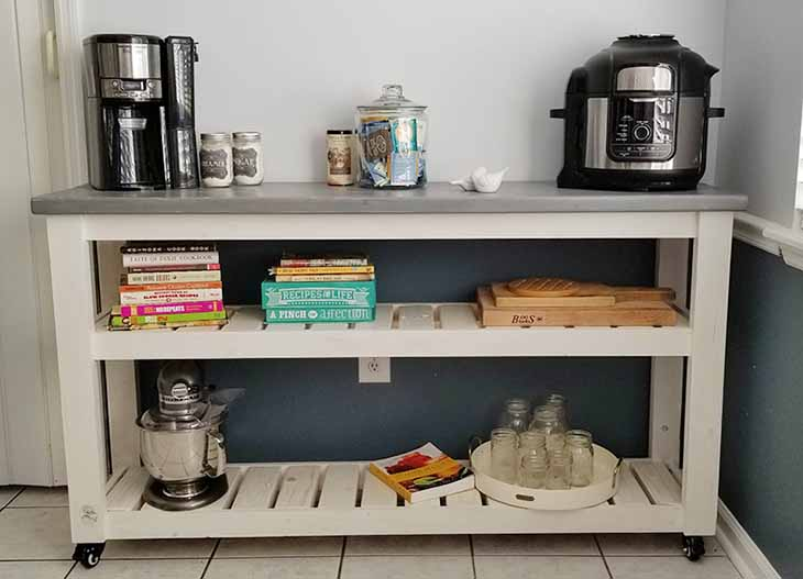 kitchen cart with wheels with coffee pot, insta pot cookbooks and cutting boards on the shelves
